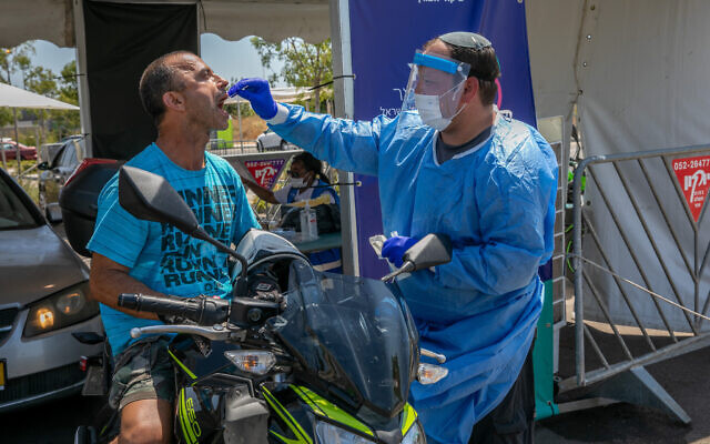 Health care workers take test samples of Israelis in a drive through complex to check if they have been infected with the coronavirus, in Modi'in, on July 21, 2021. (Yossi Aloni/Flash90)