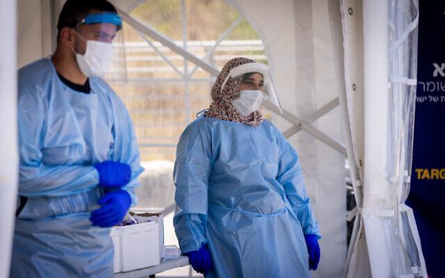 Health care workers on duty taking swabs for coronavirus tests in Jerusalem, July 22, 2021. (Yonatan Sindel/Flash90)