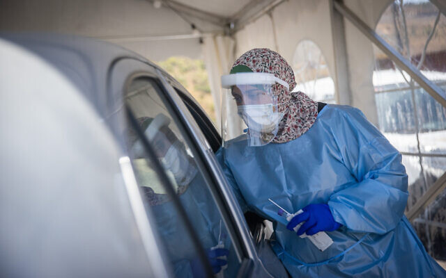 Health care workers test Israelis for COVID-19 in a Jerusalem drive through complex, July 22, 2021. (Yonatan Sindel/Flash90)