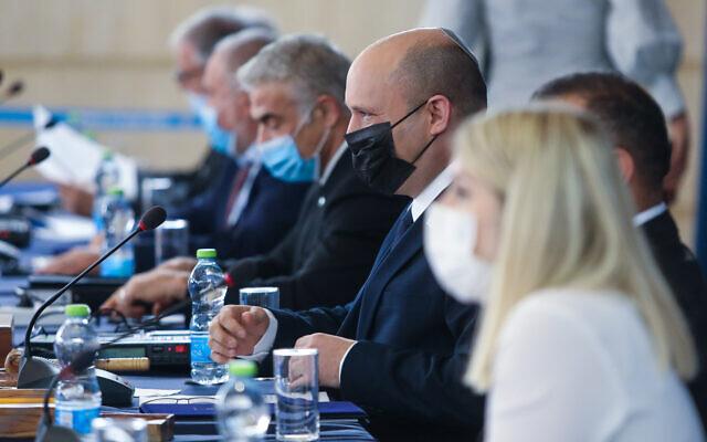 Prime Minister Naftali Bennett, center wearing black mask, during a cabinet meeting at the Foreign Ministry in Jerusalem on July 25, 2021. (Marc Israel Sellem/Pool)