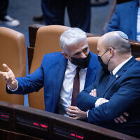 Yair Lapid, left, and Naftali Bennett seen during a plenary session at the Knesset in Jerusalem, on July 26, 2021. (Yonatan Sindel/Flash90)