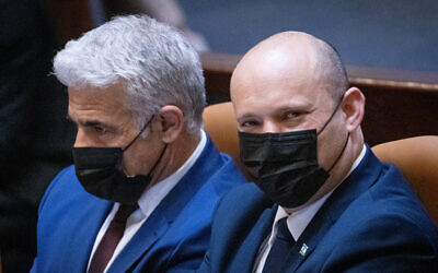Foreign Minister Yair Lapid and Israeli Prime Minister Naftali Bennett seen during a plenary session at the assembly hall of the Knesset in Jerusalem, July 26, 2021. (Yonatan Sindel/Flash90)