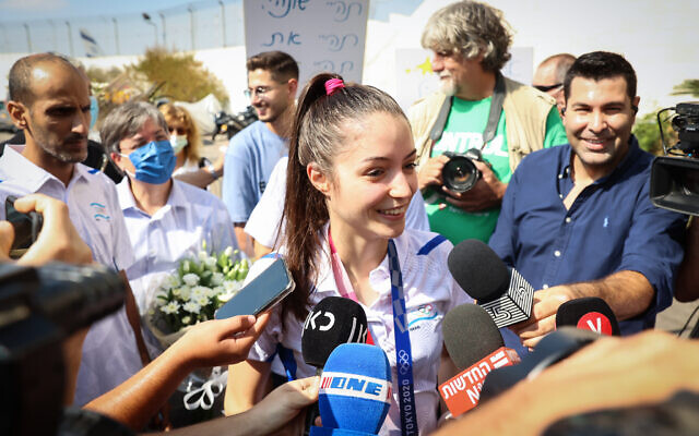 Olympic bronze medalist Avishag Semberg is greeted by the press, family and friends as she arrives at Ben Gurion Airport, on July 27, 2021. (Flash90)