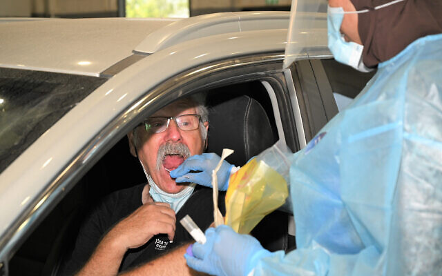 A healthcare worker takes a swab sample from a man at a drive-thru coronavirus testing site in the Golan Heights, on July 30, 2021. (Michael Giladi/Flash90)