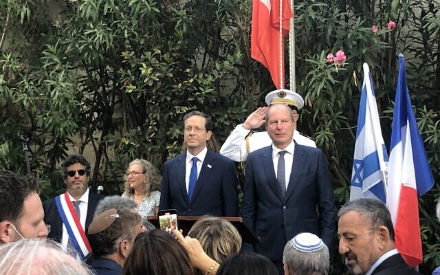 President Isaac Herzog (L) at Bastille Day celebrations at the French ambassador's residence in Jaffa, July 14, 2021. (Lazar Berman/Times of Israel)