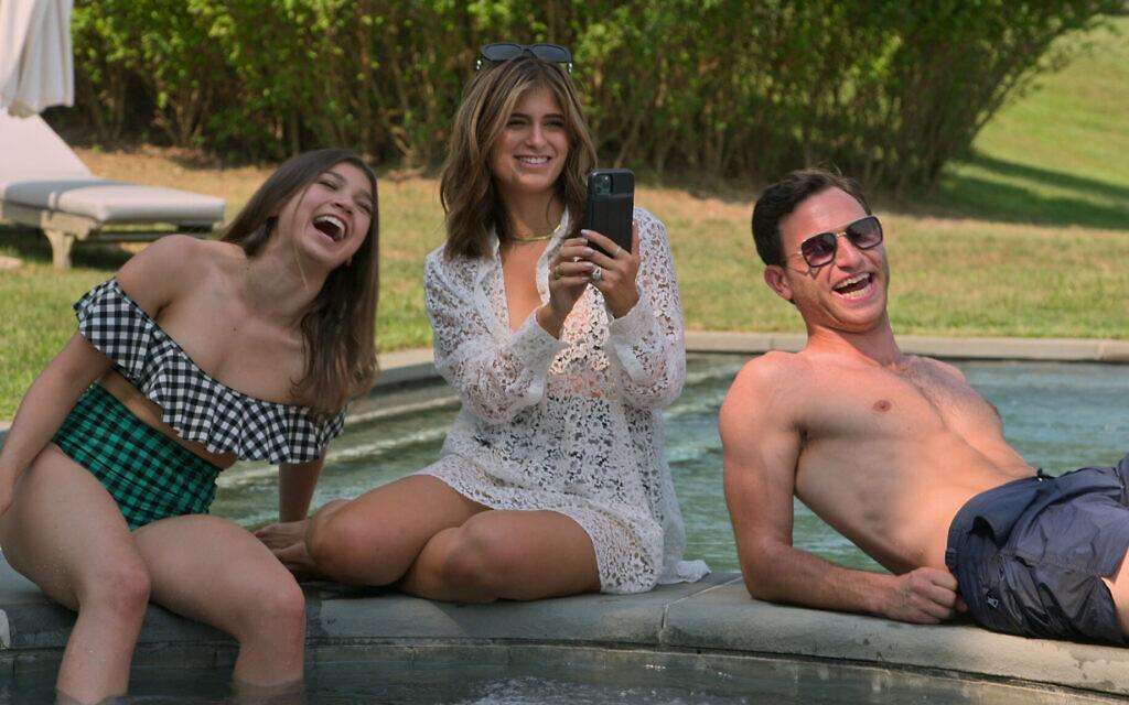 """Miriam Haart, Batsheva Weinstein and Binyamin """"Ben"""" Weinstein lounge by the pool in the Hamptons. (Courtesy Netflix)"""
