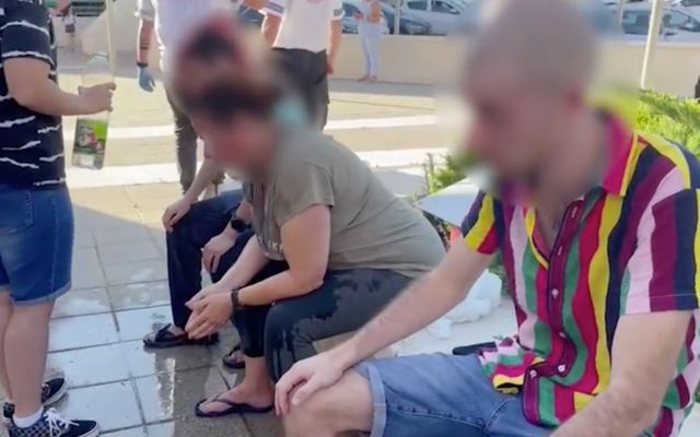 Three Ariel pride particapants are tended to after being doused with pepper spray on July 8, 2021. (Screen capture/YouTube)