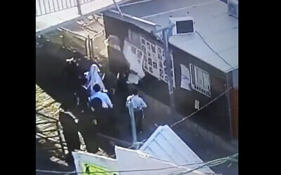 A screenshot of security camera footage shows suspects vandalizing posters of the victims of the Mount Meron disaster. (Screen capture: Twitter)