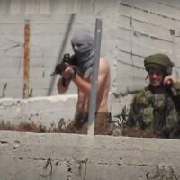 An off-duty soldier with a shirt wrapped around his face as a mask opens fire toward the village of Urif from the Yitzhar settlement on May 14, 2021. (B'Tselem)