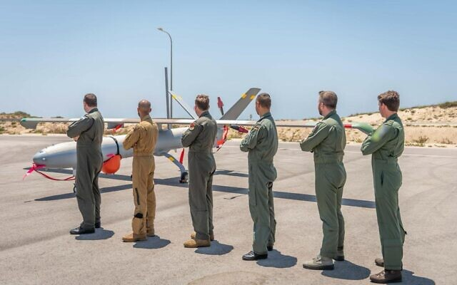 Drone pilots from five countries and Israel pose in front of a Hermes-450 unmanned aerial vehicle during an international exercise, dubbed Blue Guardian, which launched on July 12, 2021. (Israel Defense Forces)