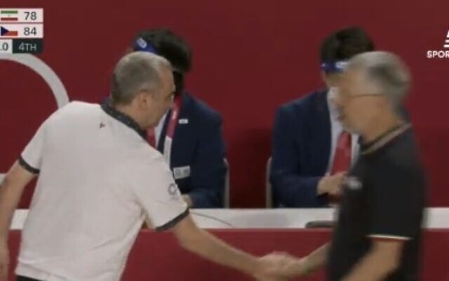 Ronen Ginzburg, the Israeli coach of the Czech national men's basketball team, shakes hands with his Iranian counterpart, Mehran Shahintab, at the Olympic Games on July 25, 2021 (Screen capture: Sports 5)