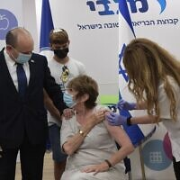 Prime Minister Naftali Bennett accompanies his mother, Myrna, as she gets a COVID-19 booster shot on August 3, 2021. (Kobi Gideon/GPO)