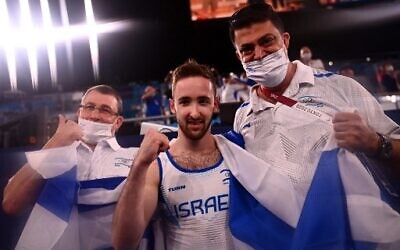 Israel's Artem Dolgopyat (C) celebrates with his team after winning the floor event of the artistic gymnastics men's floor exercise final during the Tokyo 2020 Olympic Games at the Ariake Gymnastics Centre in Tokyo on August 1, 2021. (Loic VENANCE / AFP)