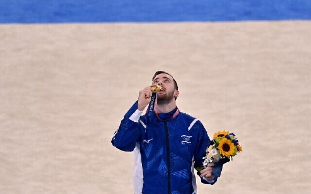 Gold medalist Israel's Artem Dolgopyat celebrates on the podium of the floor event of the artistic gymnastics men's floor exercise final during the Tokyo 2020 Olympic Games at the Ariake Gymnastics Centre in Tokyo on August 1, 2021. (Jeff PACHOUD / AFP)
