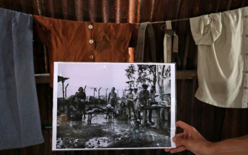 A man holds an old picture of Jews detained by British soldiers in Cyprus washing clothes at the camp, at the Jewish museum of Cyprus in the port city of Larnaca on July 26, 2021. (Christina ASSI / AFP)