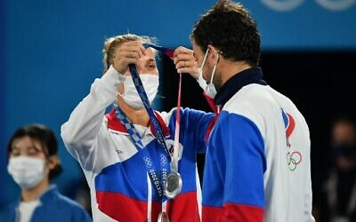 Silver medallists Russia's Elena Vesnina and Russia's Aslan Karatsev put on their respective medal during the Tokyo 2020 Olympic mixed doubles tennis medal ceremony at the Ariake Tennis Park in Tokyo on August 1, 2021. (Photo by Vincenzo PINTO / AFP)