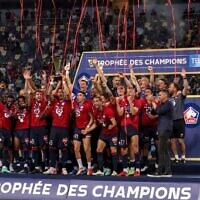Lille's players celebrate with the trophy after winning the French Champions' Trophy (Trophee des Champions) final football match between Paris Saint-Germain (PSG) and Lille (LOSC) at the Bloomfield Stadium in Tel Aviv, Israel, on August 1, 2021. (Photo by EMMANUEL DUNAND / AFP)