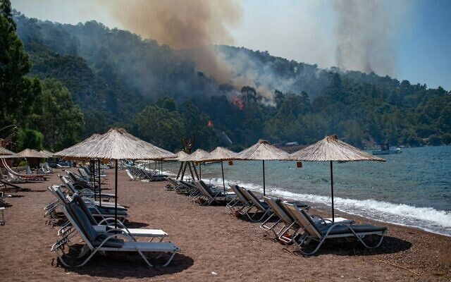 Deck chairs are seen on a beach in front of smoke and flames rising from a forest fire on August 3, 2021, in the southwestern Turkish city of Mugla, as Turkey struggles against its deadliest wildfires in decades. (Photo by Yasin AKGUL / AFP)