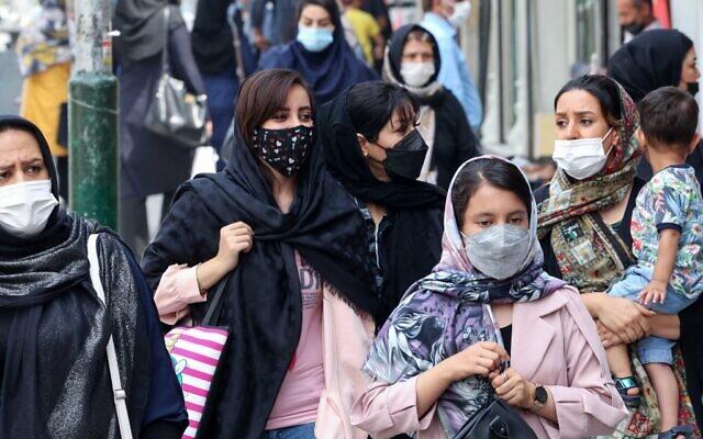 Mask-clad Iranians shop at the Tajrish Bazaar market in the capital Tehran, on August, 3 2021. (Atta Kenare/AFP)