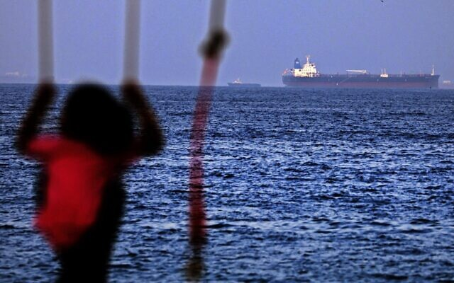 A child rides a swing as the Israeli-linked Japanese-owned tanker MT Mercer Street is seen off the port of the Gulf Emirate of Fujairah in the United Arab Emirates on  August 3, 2021 (Karim SAHIB / AFP)