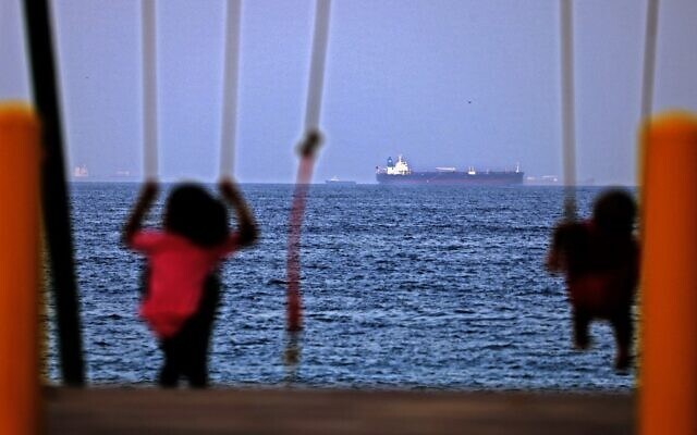 Children ride a swing as the Israeli-linked tanker MT Mercer Street is seen off the port of the Gulf Emirate of Fujairah in the United Arab Emirates, on August 3, 2021. (Karim Sahib/AFP)