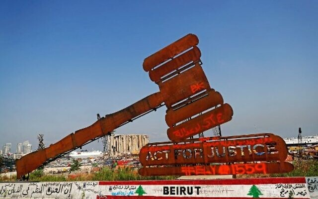 A gavel monument symbolizing justice is seen in front of the damaged grain silos at Beirut port on August 4, 2021, as Lebanon marks a year since a cataclysmic explosion ravaged the capital Beirut. (JOSEPH EID / AFP)