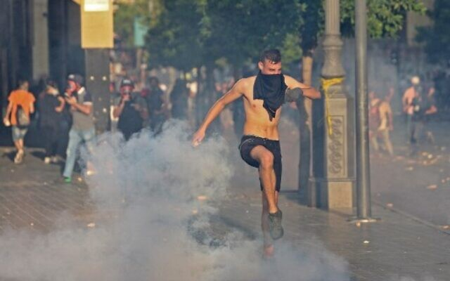 A Lebanese man kicks a teargas cannister as Lebanese army and security forces clash with demonstrators near the parliament in downtown Beirut on August 4, 2021. (AFP)