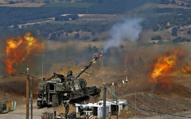 Israeli self-propelled howitzers fire toward Lebanon from a position near the northern town of Kiryat Shmona following rocket fire by the Lebanese terror group Hezbollah, August 6, 2021. (Jalaa Marey/AFP)