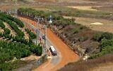 A picture taken from Lebanon's southern Marjayoun area shows an agricultural vehicle driving down a dirt road in the Israeli town of Metula along the border fence between the two countries, on August 6, 2021. (Mahmoud Zayyat/AFP)