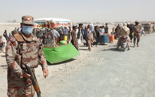 An army soldier patrols as stranded people wait for the reopening of the border crossing point which was closed by the authorities, in Chaman on August 7, 2021, after the Taliban took control of the Afghan border town in a rapid offensive across the country. (Asghar Achakzai/AFP)