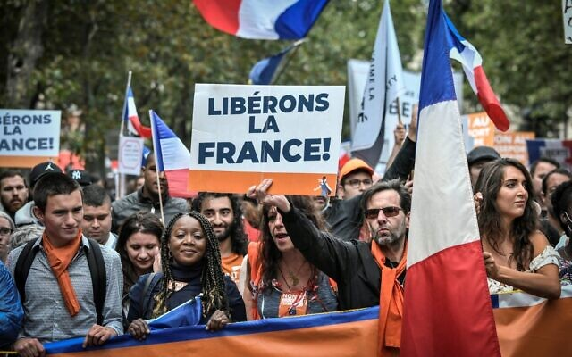 Protestors hold a French flag and a sign reading 'Liberate France' during a demonstration, part of a national day of protest against the mandatory Covid-19 health pass to access most of the public space, near Ecole Militaire in Paris on August 7, 2021. (Photo by STEPHANE DE SAKUTIN / AFP)