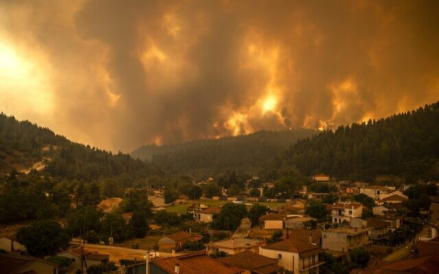 This picture taken on Evia island, the second largest Greek island, on August 8, 2021 shows a wildfire moving towards the village of Gouves. (Photo by ANGELOS TZORTZINIS / AFP)