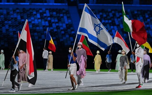 Israeli gold medalist Linoy Ashram (C) carries the national flag during the closing ceremony of the Tokyo 2020 Olympic Games, at the Olympic Stadium, in Tokyo, on August 8, 2021. (Adek BERRY / AFP)