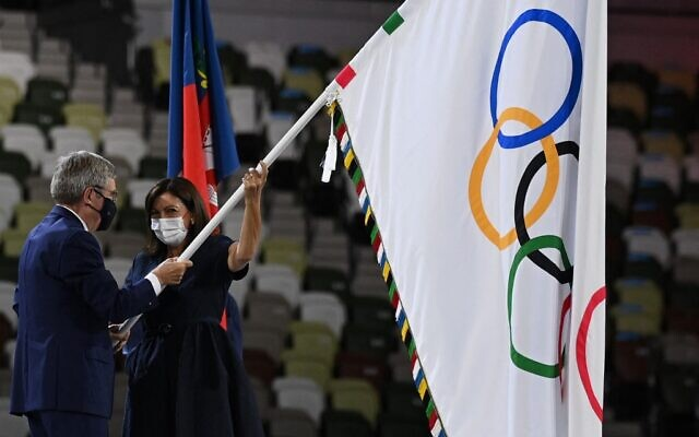 President of the International Olympic Committee Thomas Bach (L) hands-over the Olympic flag to Paris Mayor Anne Hidalgo during the closing ceremony of the Tokyo 2020 Olympic Games, at the Olympic Stadium, in Tokyo, on August 8, 2021. (Photo by Daniel LEAL-OLIVAS / AFP)