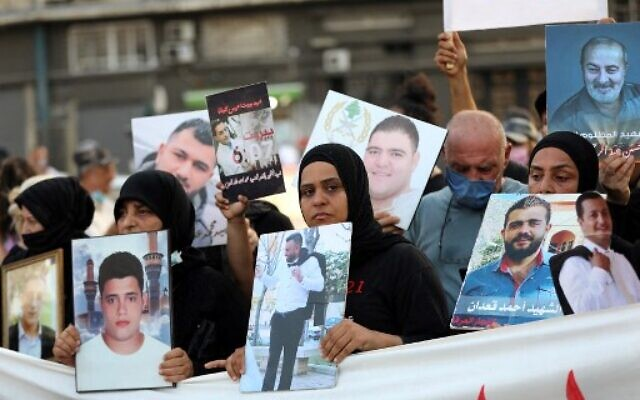 Families of the August 4 victims joined by protestors march with imitation coffins and portraits of their loved ones during a symbolic funeral procession from Beirut port on August 8, 2021, days after the first anniversary of a vast dockside explosion that left more than 200 people dead. (ANWAR AMRO / AFP)