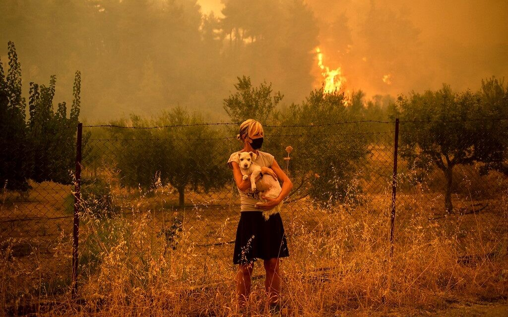 A woman holds a dog in her arms as forest fires approach the village of Pefki on Evia (Euboea) island, Greece's second largest island, on August 8, 2021 (ANGELOS TZORTZINIS / AFP)