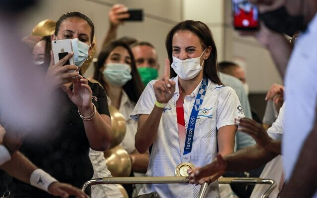 Olympic Gold medalist Linoy Ashram is greeted by press, family and friends as she arrives at Ben Gurion Airport after winning the Gold medal in the rhythmic gymnast at the Olympic Games in Japan, August 11, 2021. (Menahem KAHANA / AFP)