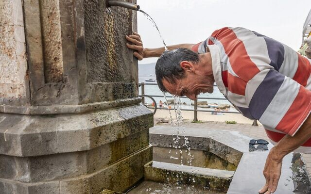 A man refreshes himself in a fountain during a hot summer day in Messina, on August 11, 2021. (Giovanni ISOLINO / AFP)