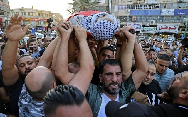Palestinians carry the body of Dia al-Sabarini, 25, during his funeral in the West Bank city of Nablus on August 11, 2021. (JAAFAR ASHTIYEH / AFP)
