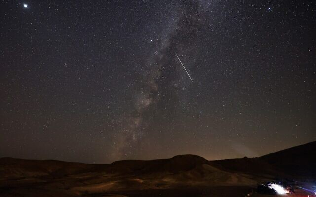 The Milky Way galaxy is pictured as a Perseid meteor streaks across the sky above the Negev desert near the Israeli city of Mitzpe Ramon, on August 13, 2021, during a yearly meteor shower (Menahem KAHANA / AFP)