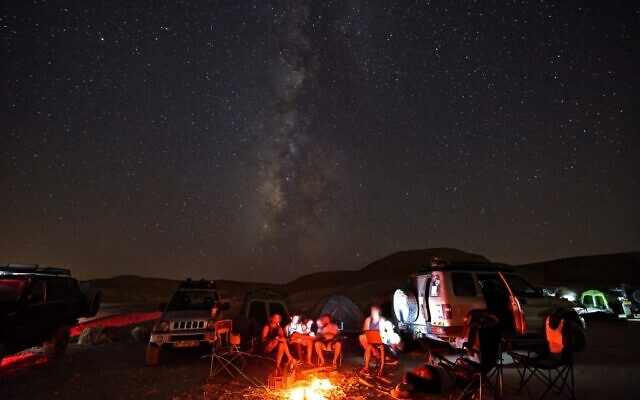 Campers gather as the Milky Way galaxy rises in the night sky above the Negev desert near the Israeli city of Mitzpe Ramon, on August 13, 2021. (Menahem KAHANA / AFP)