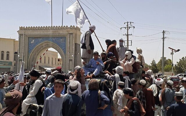 Taliban fighters stand on a vehicle along the roadside in Kandahar on August 13, 2021. (AFP)