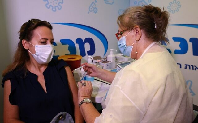 An Israeli health worker administers a third dose of the Pfizer-BioNtech COVID-19 vaccine to a woman, at the Maccabi Health Service in the Israeli town of Rishon Lezion on August 13, 2021 (AHMAD GHARABLI / AFP)