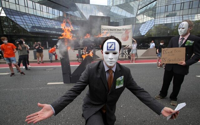 A climate activist dressed up as a banker poses in front of a burning Deutsche Bank logo in front of the bank's headquarters during a demonstration on August 13, 2021 in Frankfurt am Main, western Germany. (ARMANDO BABANI / AFP)