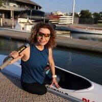 Israeli Paralympic contestant Pascale Bercovitch, 54, next to her kayak as she sets out for training in the coastal city of Tel Aviv, on August 4, 2021. (Photo by MENAHEM KAHANA / AFP)