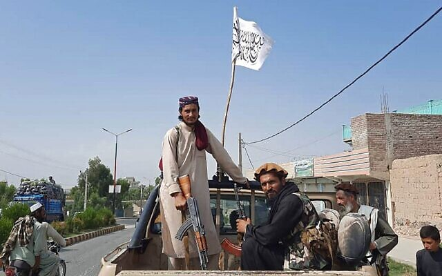 Taliban fighters drive an Afghan National Army (ANA) vehicle through the streets of Laghman province on August 15, 2021. (AFP)