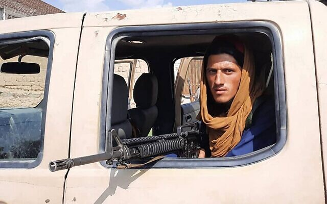 A Taliban fighter sits inside an Afghan National Army (ANA) vehicle along the roadside in Laghman province on August 15, 2021. (AFP)