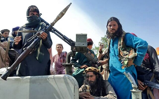 Taliban fighters sit over a vehicle on a street in Laghman province on August 15, 2021. (AFP)