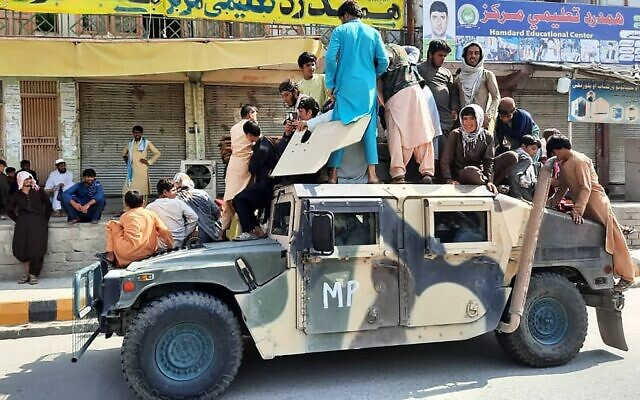 Taliban fighters and local residents sit over an Afghan National Army (ANA) vehicle along the roadside in Laghman province on August 15, 2021. ( AFP)