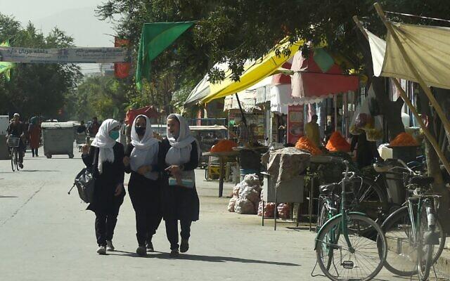 Afghan school girls walk through in a street in Kabul on August 15, 2021. (Wakil KOHSAR / AFP)